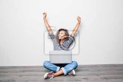 Obraz Portret szczęśliwych potomstw mieszanych ras kobiety kędzierzawy obsiadanie na podłoga z laptopem i świętuje wygranę