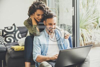Obraz Portret uśmiechnięta młoda para przy użyciu komputera przenośnego w domu kryty