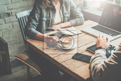 Obraz Praca w zespole. Biznesmen i businesswoman posiedzenia w tabeli w kawiarni i omówienia biznes planu. Na stole jest laptop, tablet, smartphone, notebook, filiżanka kawy. Spotkanie biznesowe partnerów w