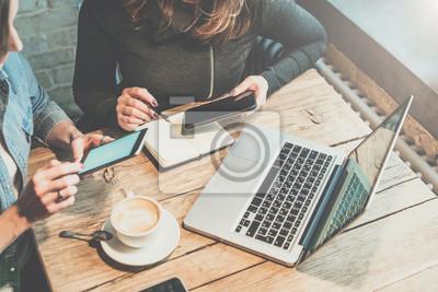 Obraz Praca w zespole. Dwóch młodych przedsiębiorców siedzi przy stole w kawiarni, spójrz na ekranie smartfona i omówić strategię biznesową. Dziewczyna notatek w notesie. Na laptopie stołu i filiżanka kawy.