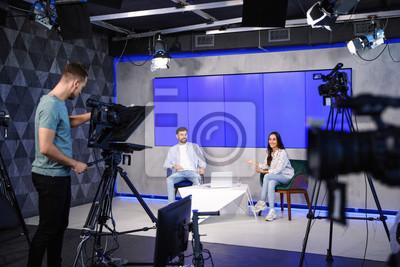 Obraz Presenters and video camera operator working in studio. News broadcasting