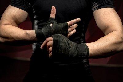 Obraz profesjonalny fighter przygotowuje się do treningu, wraping dłonie i nadgarstki