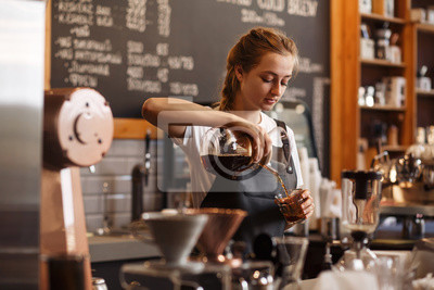 Obraz Professional barista preparing coffee using chemex pour over coffee maker and drip kettle. Young woman making coffee. Alternative ways of brewing coffee. Coffee shop concept.