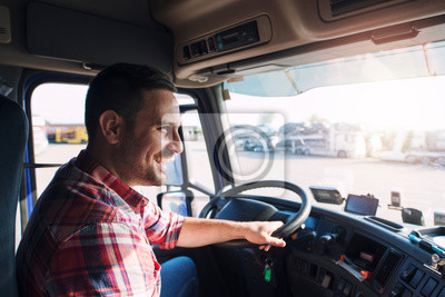Obraz Professional middle aged truck driver in casual clothes driving truck vehicle going for a long transportation route.