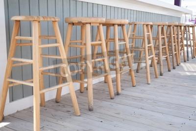 Proste drewniane stołki barowe są ustawieni na zewnątrz baru.