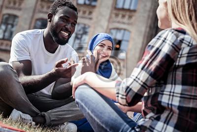 Obraz Przyjemna rozmowa. Zadowolony miły człowiek pozytywny uśmiechając się i wskazując na swojego przyjaciela, mając przyjemną rozmowę