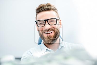 Obraz Przystojny biznesmen z wielkim uśmiechem siedzi na fotelu dentystycznym