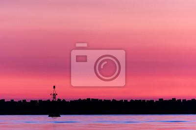 Purpurowy zachód słońca z ptakami wznosi się na latarni