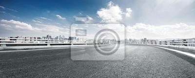 Obraz Pusta droga i pejza? Nowoczesnego miasta przed chmurnym niebie
