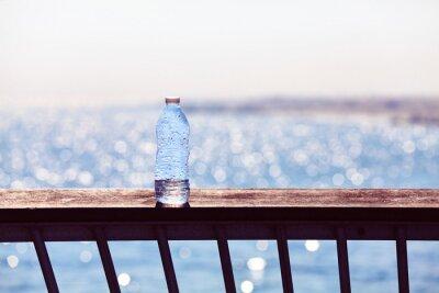 Pusta plastikowa butelka pozostawiona na balustradzie molo o zachodzie słońca, selektywne focus, stosowane tonowanie kolorów.