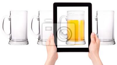 pusty i jeden pełny piwo na ekranie tabletu komputerowego