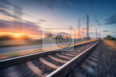 Railroad and beautiful blue sky with clouds at sunset with motion blur effect in summer. Industrial landscape with railway station and blurred background.  Railway platform in speed motion. Concept