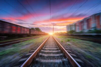 Railroad and beautiful sky with clouds at sunset with motion blur effect in summer. Industrial landscape with freight train, railway station and blurred background.  Railway platform in speed motion