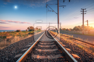 Railroad and blue sky with moon at sunset. Summer rural industrial landscape with railway station, sky with clouds and gold sunlight, green grass. Railway platform. Transportation. Heavy industry