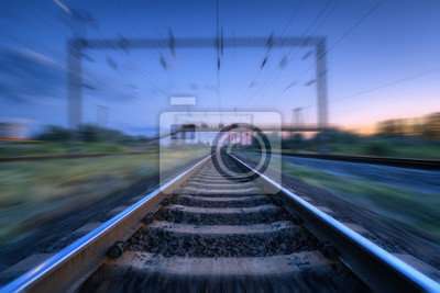 Railroad and blue sunset sky with clouds with motion blur effect. Industrial landscape with railway station and blurred background at twilight. Railway platform in move. Transportation. Speed motion