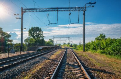 Railway station at bright sunny day in summer. Railroad in Europe. Heavy industry. Industrial landscape with railway platform, green trees, blue sky with clouds and sunlight. Transportation