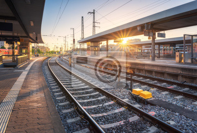 Railway station at sunset. Industrial landscape with railroad, railway platfform, buildings, blue sky with orange sunlight in the evening. Railway junction in summer in Europe. Transportation