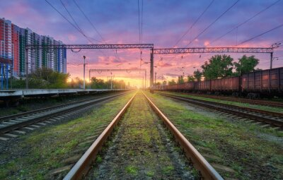 Railway station with freight trains at colorful sunset. Railroad in summer. Heavy industry. Industrial landscape with train, green grass, railway platform, purple sky with pink clouds. Transportation