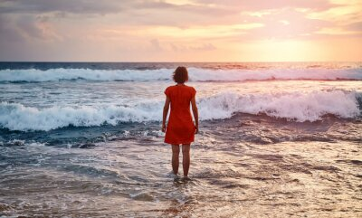 Rear view of a woman in orange dress standing still in the ocean at sunset.