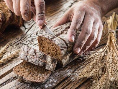 Obraz Ręce mężczyzny cięcia chleb na drewnianej desce.