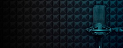 Obraz Recording studio microphone on black acoustic foam background with blue light and copy space