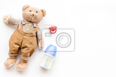 Obraz Ręcznie robione zabawki dla noworodka. Miś. Butelka do karmienia mlekiem i smoczkiem. Makieta widok z góry białe tło