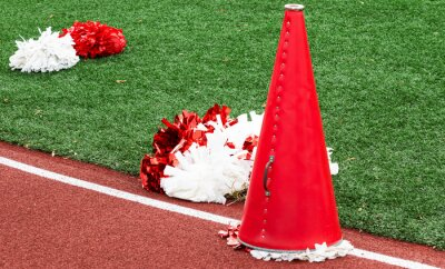 Obraz Red and white cheerleading megaphone and pop poms