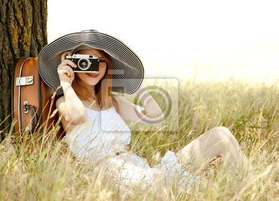 Redhead dziewczyna siedzi w pobliżu drzewa z rocznika kamery.