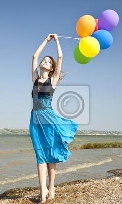 Redhead dziewczyny z kolorowych balonów na wybrzeżu.