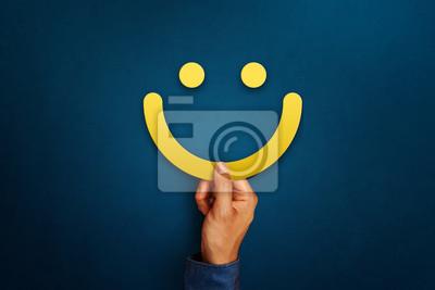 Obraz Ręka klienta pokazuje informację zwrotną ze znakiem uśmiechniętej buźki. Ocena usług, koncepcja satysfakcji