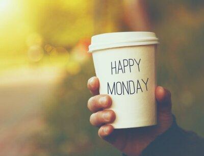 Obraz Ręka trzyma papierowy kubek kawy z Happy Monday motywacyjna