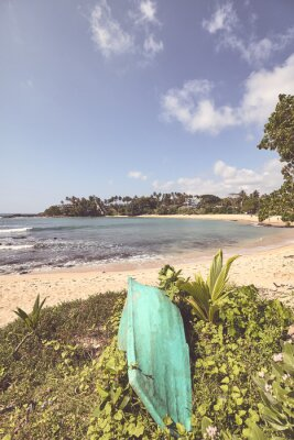 Retro color stylized picture of a tropical beach with a small boat.