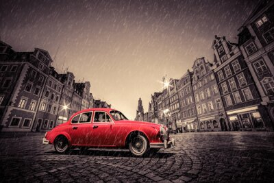 Retro czerwony samochód na brukowanej zabytkowego starego miasta w deszczu. Wrocław, Polska.