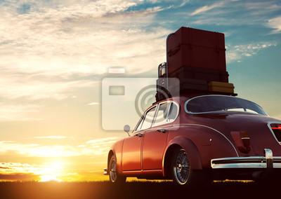 Obraz Retro czerwony samochód z bagażu na bagażniku dachowym o zachodzie słońca. Podróże, wakacje pojęcia.