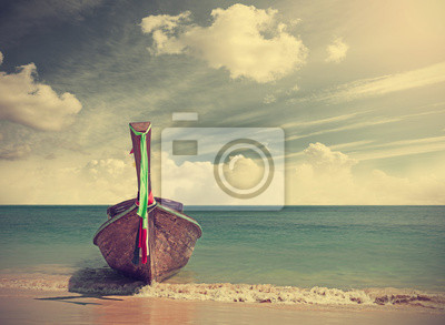 Retro filtered picture of a wooden boat on beach.