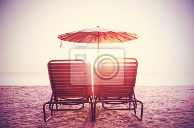 Retro filtered picture of beach chairs and umbrella on sand at s