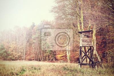 Retro filtrowane zdjęcie ambony myśliwskiej w lesie.