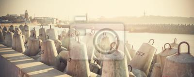 Retro filtrowane zdjęcie bloku betonowym falochronie.