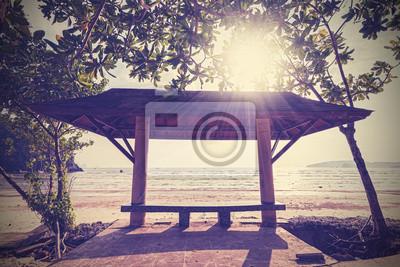 Retro filtrowane zdjęcie ławce nad morzem o zachodzie słońca.