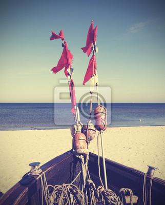 Retro filtrowane zdjęcie łodzi rybackiej na plaży.