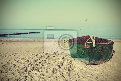 Retro filtrowany obraz starej łodzi zardzewiały stali na plaży.