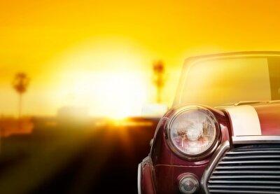 Obraz Retro reflektorów samochodu na ulicy w tle zachodu słońca