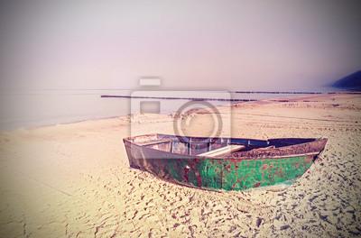 Retro stary zardzewiały efekt filmu na stalowej łodzi na plaży.