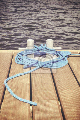 Retro stonowanych obraz klucza z niebieską liną na drewnianym molo, koncepcja bezpiecznej podróży.
