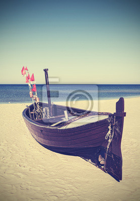 Retro stonowanych obraz łodzi rybackiej na plaży.