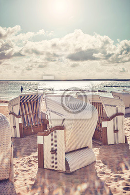 Retro stylized picture of wicker beach chairs on a beach against the sun with lens flare.
