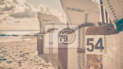 Retro stylized picture of wicker beach chairs on a beach against the sun with lens flare, selective focus.