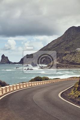 Retro toned picture of a scenic road on the Atlantic Ocean coast of Tenerife, Spain.