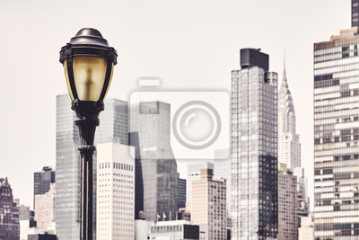 Retro toned picture of a street lamp with New York City blurred skyline in background, USA.