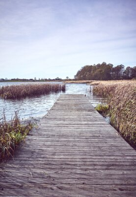 Retro toned picture of a wooden pier by lake in Autumn